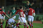 Wales scrum half Rhodri Williams kicks the ball away from the back of the ruck under pressure from Ireland wing Rory Scholes..Under 20 Six Nations.Wales v Ireland.Eirias - Colwyn Bay.01.02.13.©Steve Pope