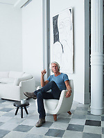 Interior designer, Kevin Roberts, in a  1950s armchair by Joseph-André Motte. A drawing by Thomas Houseago hangs on the wall behind.