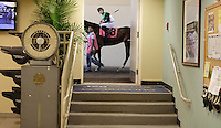 Riding by the doorway of the jockeys lounge a horse and rider make their way through the tunnel and out to the track.
