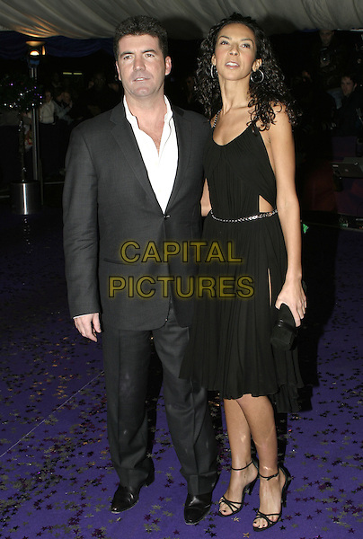 SIMON COWELL & TERRI SEYMOUR.British Comedy Awards 2004, London Television Studios, London, December 22nd 2004..full length black dress terry seymore cut out sides couple .Ref: AH.www.capitalpictures.com.sales@capitalpictures.com.©Capital Pictures.