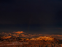 73075002 clearing summer monsoon storm over theaquarius plateau and the hoodoods with a partially formed rainbow and dark foreboding skies seen from sunset point in bryce canyon national park utah
