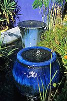 Blue ceramic pots and some aquatic plants combine to make an unusual fountain and pond when combined with a blue wall at the demonstration garden created by Mike Shoup at his Antique Rose Emporium nursery in San Antonio, Texas.