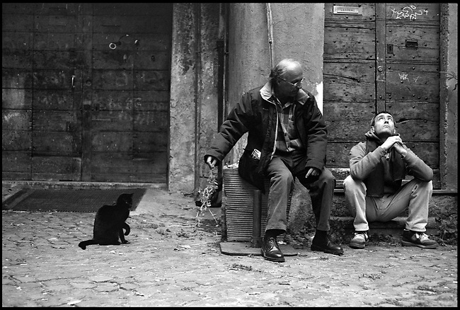 Two men and a black cat in a traditional courtyard in Rome's Trastevere quarter. Rome, Italy, 2008.