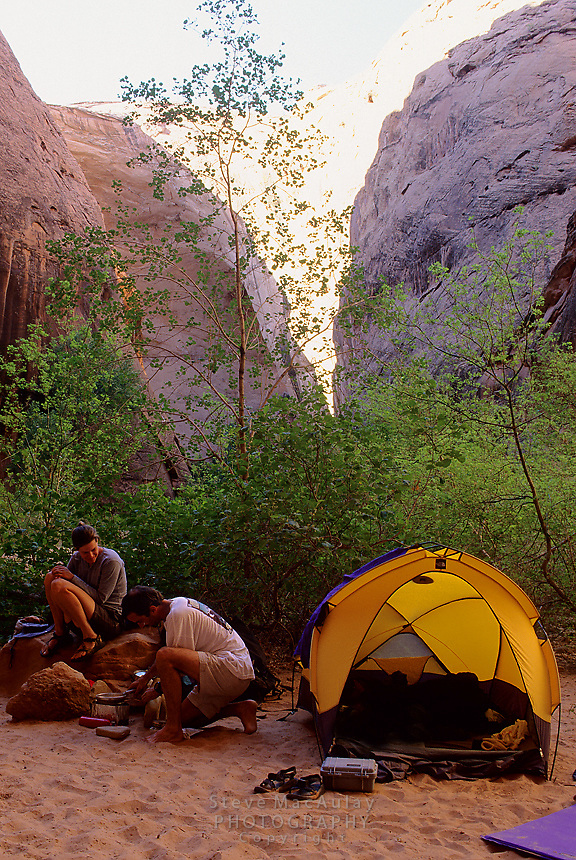 Man and woman backpackers prepare a meal on campstove in idylic campsite, Coyote Gulch; Grand Staircase Escalante National Monument; Utah