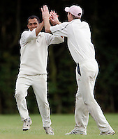 N Azah (L) of Wembley is high-fived after taking a catch to dismiss North London batsman Byron Hackshall during the Middlesex County League Division three game between Wembley and North London at Vale Farm, Wembley on Sat August 6, 2011