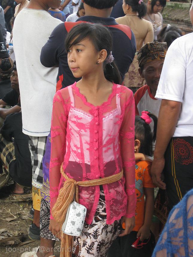 girl watching cremation ceremonies in village Mas, Bali, archipelago Indonesia