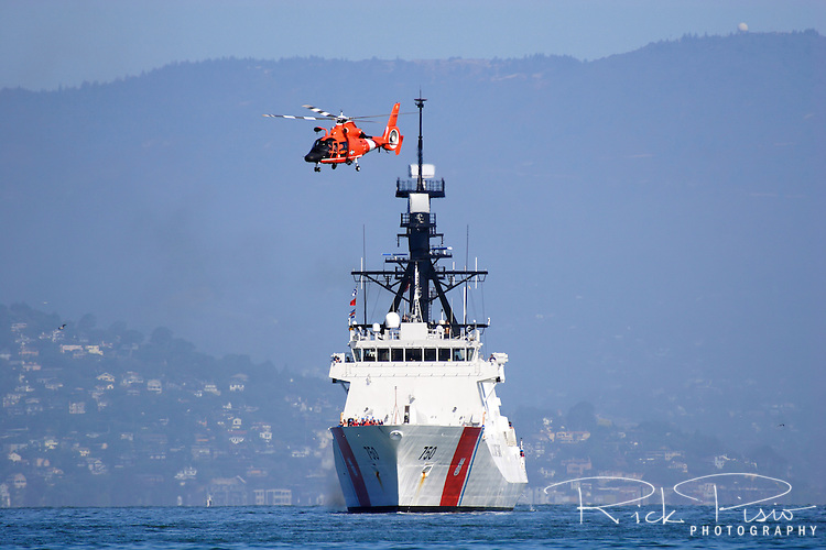 The United States Coast Guard Cutter Bertholf (WMSL 750) is escorted through San Francisco Bay by a HH-65C Dolphin helicopter at the conclusion of the voyage to it new home port in Alameda, California. The Bertholf was launched on September 29, 2006 at the Ingalls Shipyard in Pascagoula, Mississippi and was christened on November 11, 2006. It is the first of the Legend class maritime security cutters to enter the Coast Guard fleet. Photographed 7/23/08