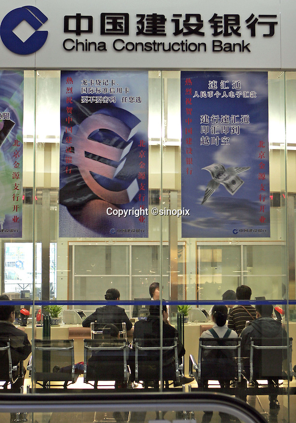 People are served in a branch of China Construction Bank in a Beijing shopping mall, China.<br /> 03-JAN-05