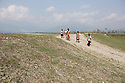India – West Bengal: A group of stonecrushers coming back from work along the Diana riverbed at Red Bank Tea Estate, in the Dooars region. The garden, which houses 888 workers out of a population of 5,000 people, has been closed since 2013, forcing its workers to resort to stonecrushing along the riverbanks in order to survive. At the end of 2014, the tea estate was taken over by the government, in order to initiate emergency relief procedures for its population.