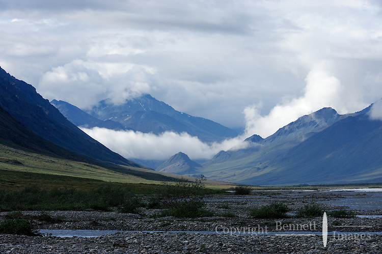 Sun and clouds mix on a summer day along the Hulahula River valley as it flows north from Alaska's Brooks Range mountains to the Coastal Plain in the Arctic National Wildlife Refuge.