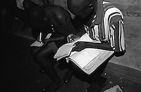 Doing schoolwork before bed at the Doctors Without Borders (MSF; Medecins Sans Frontieres) tent compound. This compound is one of the few places children, known as Night Commuters, can find protection every  night to avoid being abducted by the Lords Resistance Army (LRA) in Northern Uganda. The LRA is primarily made up of abducted youth. Night Commuters find much more than safety in the compounds, they also find friendships, activity and fellowship. Tens of thousands of children, on average, make this exodus every evening. The war in Northern Uganda has been transpiring for two decades. Lachor, Gulu District, Uganda, Africa. July 2004 © Stephen Blake Farrington