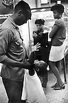 WASHINGTON DC - USA 1969. LATE AT NIGHT IN A GREYHOUND BUS STATION, AN AFRICAN AMERICAN FATHER AND HIS YOUNG DAUGHTER PLAY TOGETHER, WHILE TWO OLDER SISTERS LEAN AGAINST A PIN BALL MACHINE