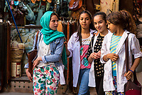 Fes, Morocco.  Young Women in Modern Moroccan Dress Styles Walking in the Old City.
