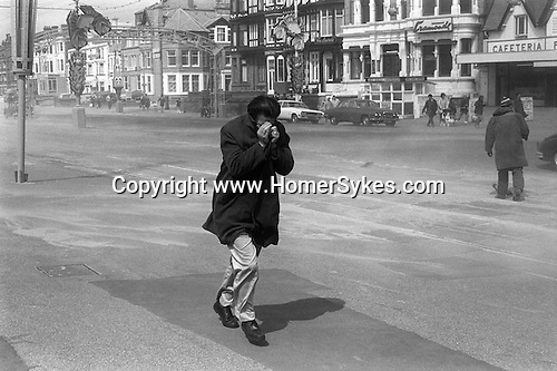 BLACKPOOL, LANCASHIRE, ENGLAND   1970: A strong wind blows dry sand off the beach and onto the Golden Mile promenade. A man hides his face in his coat against the stinging wind blown sand particles.