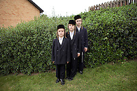 Hasidic children from the Englander family line up for a portrait, dressed ready for dinner of the evening of Shabbat. Hasidic families stay in Pentre Jane Morgan university accommodation when they holiday in Aberystwyth. Every other day, bread, milk and other supplies are brought from Kosher shops in London and resold from one of the rented houses on the campus.
