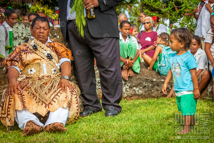 A young boy approaches Makirau Haurua during the latter's investiture with the Teurukura Ariki title, Aitutaki Island, Cook Islands.