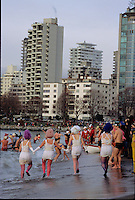 Women frolicking in underwear on the beach at the Polar Bear Swim, New Years Day, English Bay, Vancouver, BC.