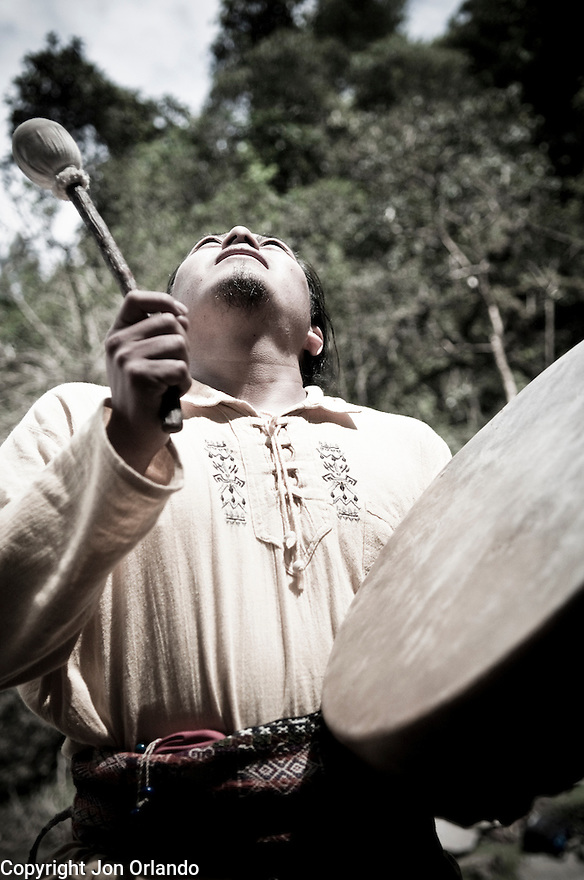Guillermo Santillán drums during a ceremony honoring a waterfall.