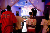 Trinidad and Tobago fans stand for their national anthem before the start of their World Cup match against England on June 15, 2006 at Reign, a New York City nightclub.<br /> <br /> The World Cup, held every four years in different locales, is the world's pre-eminent sports tournament in the world's most popular sport, soccer (or football, as most of the world calls it).  Qualification for the World Cup is open to any country with a national team accredited by FIFA, world soccer's governing body. The first World Cup, organized by FIFA in response to the popularity of the first Olympic Games' soccer tournaments, was held in 1930 in Uruguay and was participated in by 13 nations.    <br /> <br /> As of 2010 there are 208 such teams.  The final field of the World Cup is narrowed down to 32 national teams in the three years preceding the tournament, with each region of the world allotted a specific number of spots.  <br /> <br /> The World Cup is the most widely regularly watched event in the world, with soccer teams being a source of national pride.  In most nations, the whole country is at a standstill when their team is playing in the tournament, everyone's eyes glued to their televisions or their ears to the radio, to see if their team will prevail.  While the United States in general is a conspicuous exception to the grip of World Cup fever there is one city that is a rather large exception to that rule.  In New York City, the most diverse city in a nation of immigrants, the melting pot that is America is on full display as fans of all nations gather in all possible venues to watch their teams and celebrate where they have come from.