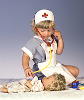 A young girl in a nurses costume plays with her doll and a stethoscope