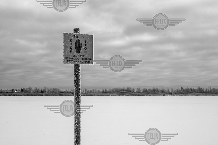 A sign stuck in ice indicates the Russian border.