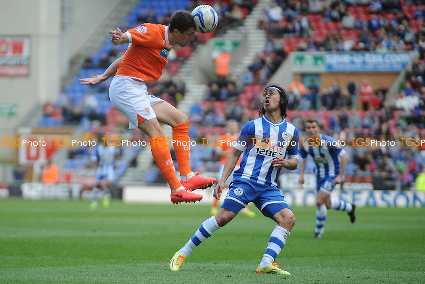 Craig Cathcart of Blackpool heads clear from Roger Espinoza of Wigan Athletic - Wigan Athletic vs Blackpool- Sky Bet Champiosnhip Football at the DW Stadium, Wigan - 26/04/14 - MANDATORY CREDIT: Greig Bertram/TGSPHOTO - Self billing applies where appropriate - 0845 094 6026 - contact@tgsphoto.co.uk - NO UNPAID USE