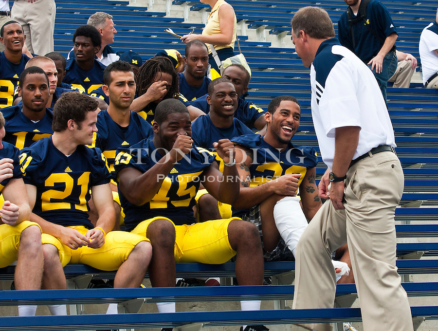 Michigan linebacker Obi Ezeh (45) and safety Troy Woolfolk, center, chat with head coach Rich Rodriguez, right, as they wait for a team photo at the annual NCAA college football media day, Sunday, Aug. 22, 2010, in Ann Arbor, Mich. Woolfolk suffered a lower leg injury during fall camp and may be out of the season. (AP Photo/Tony Ding)