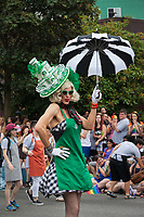 Man wearing green Starbucks hat and apron, black and white dress and umbrella, Seattle PrideFest 2015, Washington State, WA, America, USA.