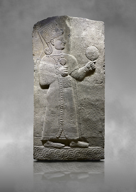 Hittite relief sculpted orthostat stone panel of Long Wall Basalt, Karkamıs, (Kargamıs), Carchemish (Karkemish), 900-700 B.C. Anatolian Civilizations Museum, Ankara, Turkey.<br /> <br /> Goddess Kubaba. Goddess is depicted from the profile. The part below the chest of the relief is broken. She holds a pomegranate in her hands on her chest. She carries a one-horned headdress on her head. Her braided hair hangs down to her shoulder. The text in the hieroglyphics is not understood. The lower part of the relief has been restored. <br /> <br /> On a grey art background.