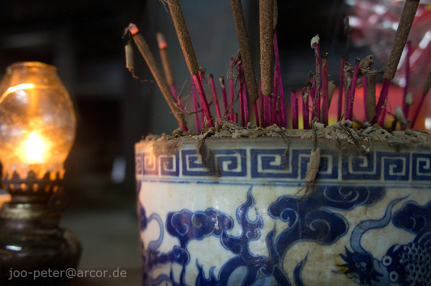 close-up of burning incent sticks in a shrine in Tu bDuc tomb with  chinese porcelain goods and petroleum a shining lamp, city Hue, Vietnam. Vietnamese belief is a blend of Buddhism, Taoism and animism.