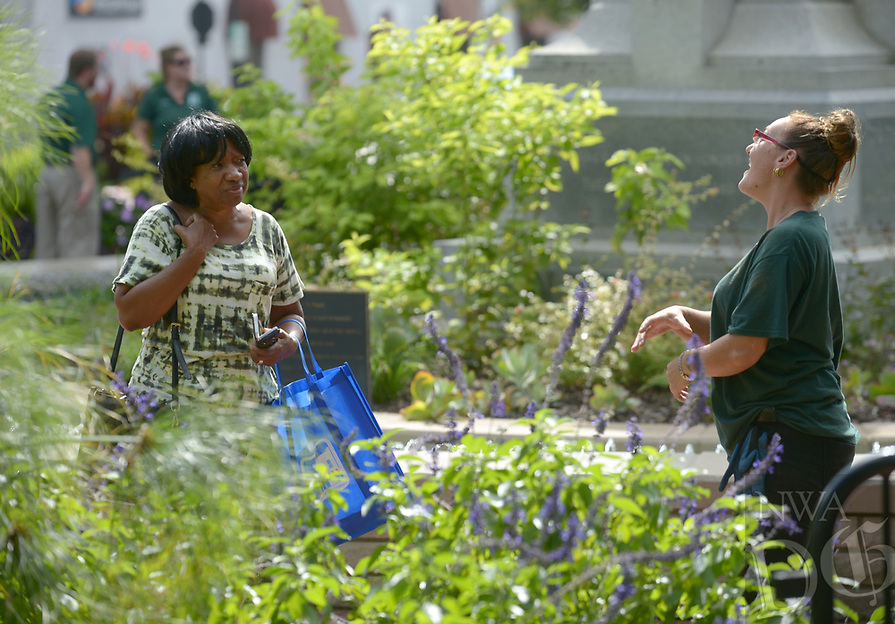 NWA Democrat-Gazette/ANDY SHUPE<br /> Honeysue Miller (right), a horticulturist with the city of Bentonville, laughs Thursday, Oct. 4, 2018, while answering questions for Diane Riddick (left) and her husband, Vincent, (not pictured) after visiting the Walmart Museum on the Bentonville square. The Riddicks are visiting the area from their home in Ludowici, Ga., and are checking off a few bucket-list travel items, including a museum and historical sites on Historic Route 66 in Kansas and Oklahoma and a trip to Branson, Mo.