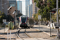 MetroRail train speeds through downtown Austin on 4th Street past the Austin Convention Center.