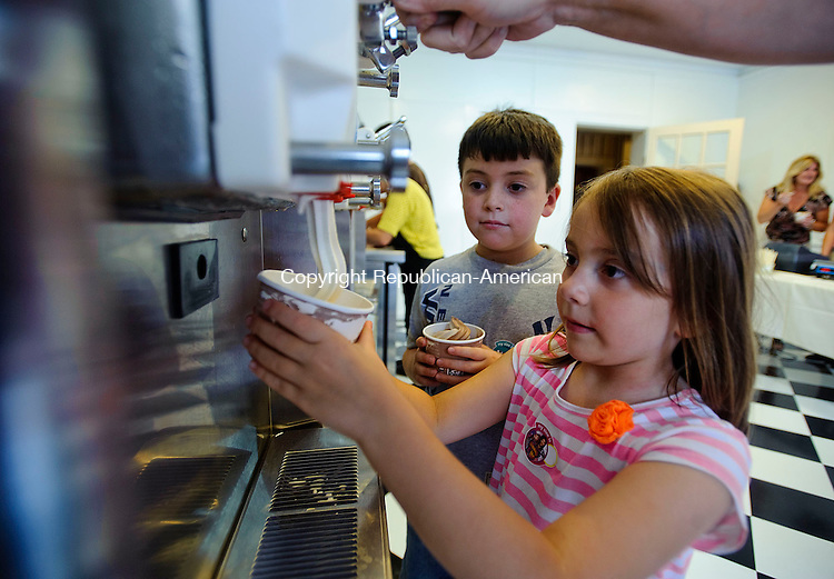 "TORRINGTON, CT -06 SEPTEMBER 2012--090612JS05- Mason Skutt, 8, left, looks as as his sister Hayley Skutt, 6, holds the cup while her mother Mindy Skutt helps her get a serving of frozen yogurt during the opening of Yankee Yogurt at the Yankee Pedlar Inn in Torrington on Thursday. The opening was part of coordinated outdoor ""happy hour"" event between Bogey's, Yankee Yogurt, Remember When and the Crystal Room. .Jim Shannon Republican-American"