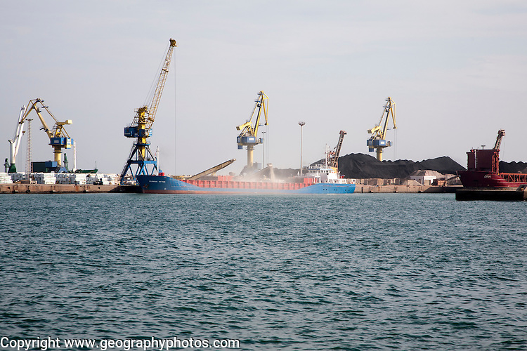 Cranes loading bulk carrier ship with rock ore at the port of Beni Ansar, Morocco, north Africa,