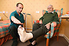 Elderly man with a foot in plaster; taking part in a physiotherapy session,