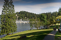 Visitors walking along path by the water amongst the trees  in Deep Cove, Burrard Inlet,Vancouver, British Columbia, Canada.