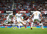 Dimitri Payet of West Ham United passes the ball under pressure from Leroy Fer and Wayne Routledge of Swansea   during the Barclays Premier League match between West Ham United and Swansea City  played at Boleyn Ground , London on 7th May 2016