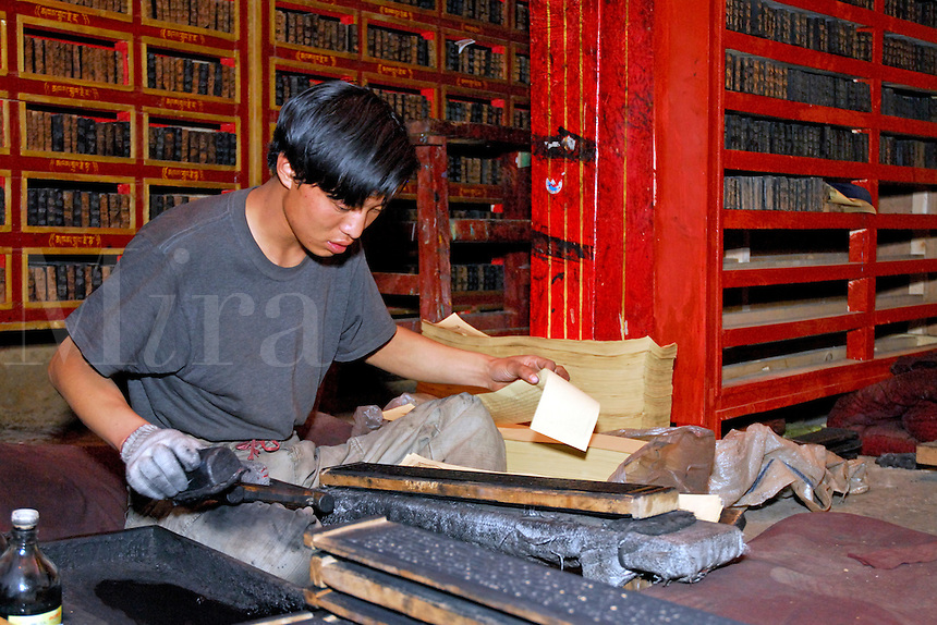 Different prayer texts fill the shelves as printer selects paper to rub over inked wooden block to produce one sheet of a prayer book, printing room, Sera Monastery, Lhasa, Tibet, China.