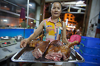 A woman holds a tray of doh meat during the Yulin Dog Meat Festival, Yulin, Guangxi Province, China, 21 June 2016.<br /> <br /> Photo by STR / Sinopix