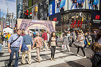 "Pedestrians cross 42nd Street in Times Square in New York during a ""Best of France"" festival on Sunday, September 27, 2015. (© Richard B. Levine)"