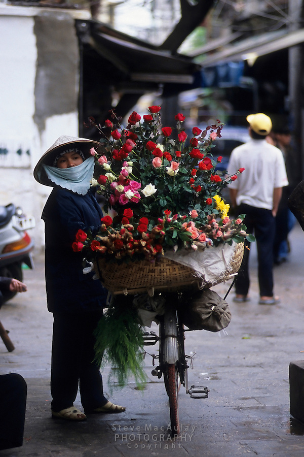 Rose seller with her basket of flowers on back of bicycle, Hanoi, Vietnam
