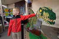 NWA Democrat-Gazette/BEN GOFF @NWABENGOFF<br /> Nathan Adams, 7, of Bentonville poses with a life-size velociraptror made from legos in the Jurassic World booth on Friday Nov. 6, 2015 during Downtown Bentonville, Inc.'s First Friday: Toyland on the Bentonville Square. Walmart toy vendors displayed a variety of their new offerings at the event ahead of the holiday shopping season.