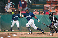 Helena Brewers center fielder Pablo Abreu (12) follows through on his swing in front of catcher Javier Guevara (6) during a Pioneer League game against the Grand Junction Rockies at Kindrick Legion Field on August 19, 2018 in Helena, Montana. The Grand Junction Rockies defeated the Helena Brewers by a score of 6-1. (Zachary Lucy/Four Seam Images)