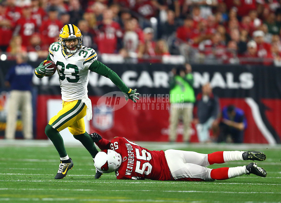 Jan 16, 2016; Glendale, AZ, USA; Green Bay Packers safety Micah Hyde (33) avoids the diving tackle attempt of Arizona Cardinals linebacker Sean Weatherspoon (55) during the NFC Divisional round playoff game at University of Phoenix Stadium. Mandatory Credit: Mark J. Rebilas-USA TODAY Sports
