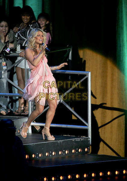 JESSICA SIMPSON.Performs live during her Reality Tour 2004 at The Pacific Ampitheatre in Costa Mesa, California .July 31,2004 .stage, music, concert, gig, singing, full length, pink dress, flowing, layered,  platform shoes.www.capitalpictures.com.sales@capitalpictures.com.Supplied By Capital Pictures