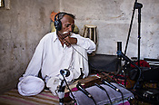 66-year-old Manganiyar artist, Lakha Khan listens to the field recording of his Sarangi in his house in Raneri village of Jodhpur district in Rajasthan, India. Photo: Sanjit Das/Panos