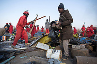 A resident grabs what he can as the Red Ants evict people and destroy an informal settlement near Pomona. <br />