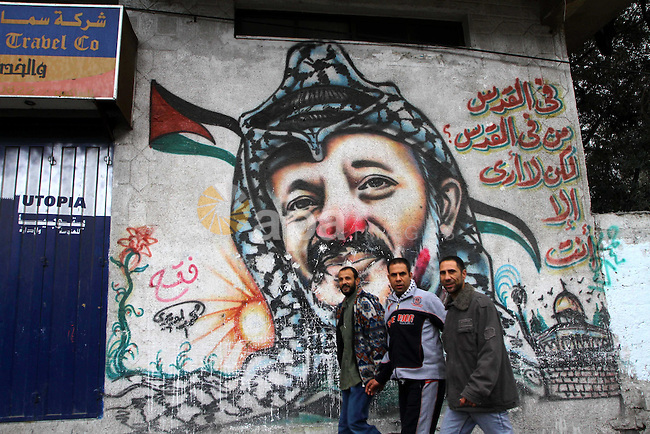 Palestinian men walk in front of a mural of the Palestinian Leader Yasser Arafat, in Gaza City on January 1, 2011. Palestinians celebrating the 46th anniversary of the founding of the Palestinian National Liberation Movement (Fatah). Photo by Ashraf Amra
