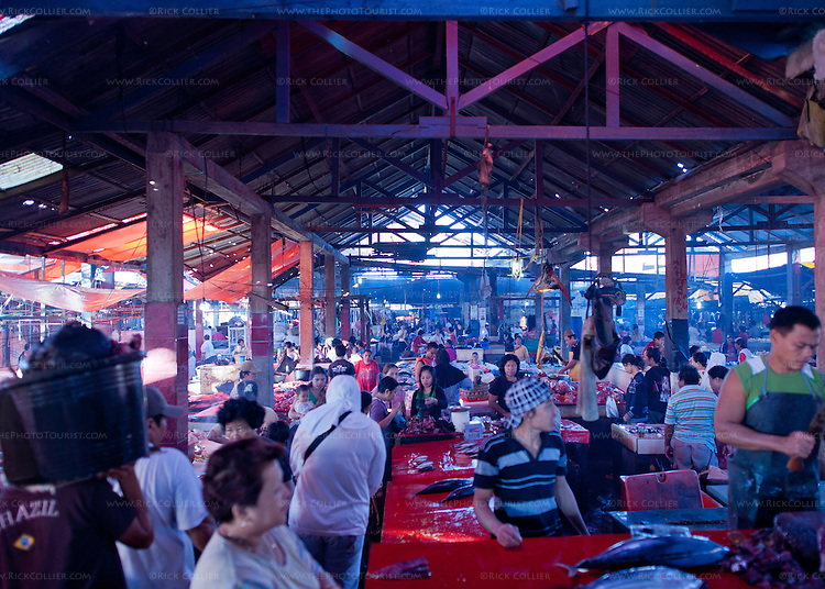 Shoppers mingle with tradesmen and sellers in the open-air main food market at Bitung City, North Sulawesi, Indonesia.
