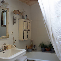 A detail of the corner of a traditional bathroom with tiled walls. A small cupboard is placed on a wall above a bath and a mirror hangs above a pedestal washbasin.